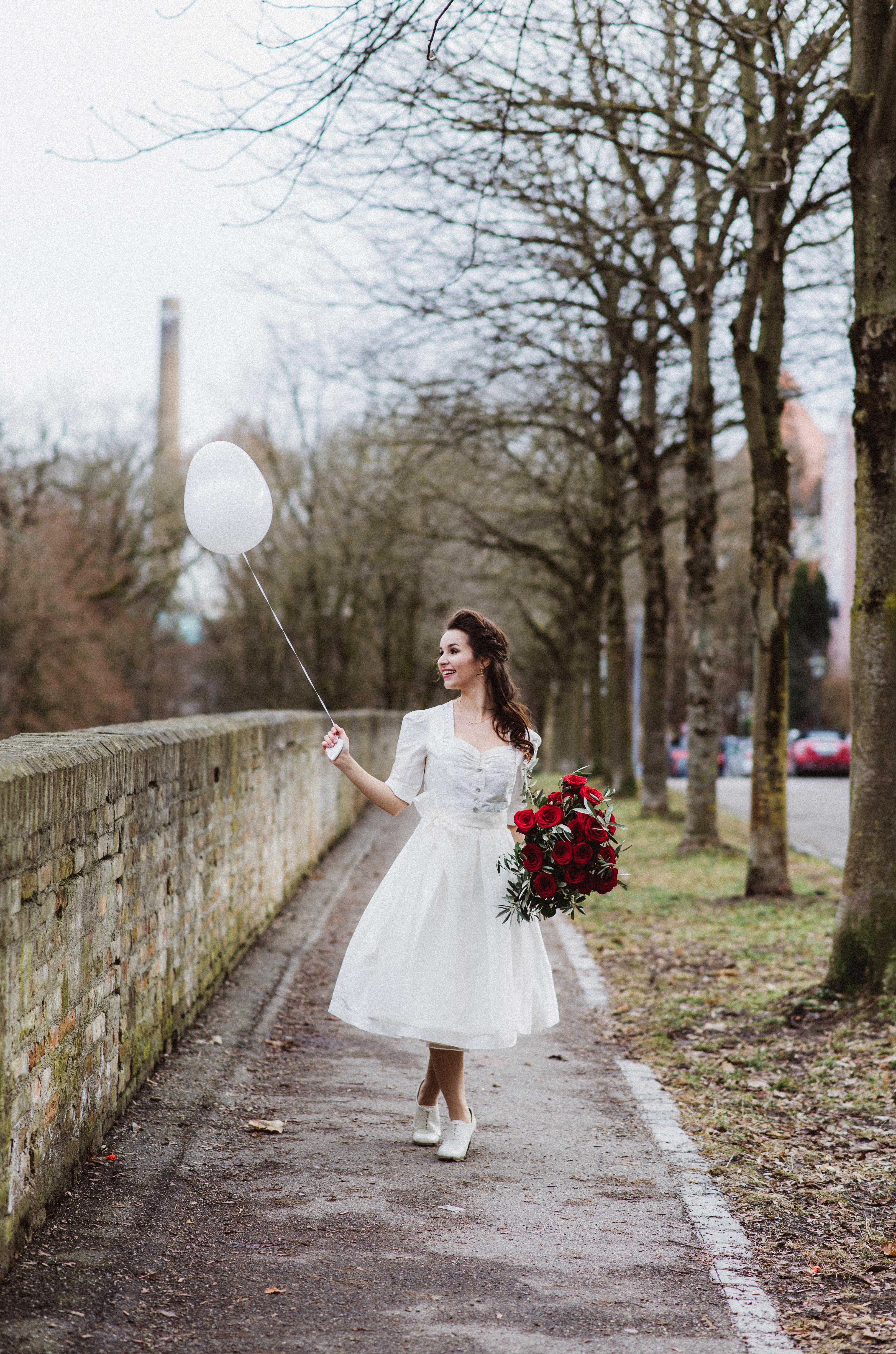 Hochzeitsdirndl weiß von Ninnerl Dirndl Brautstrauß rote Rosen