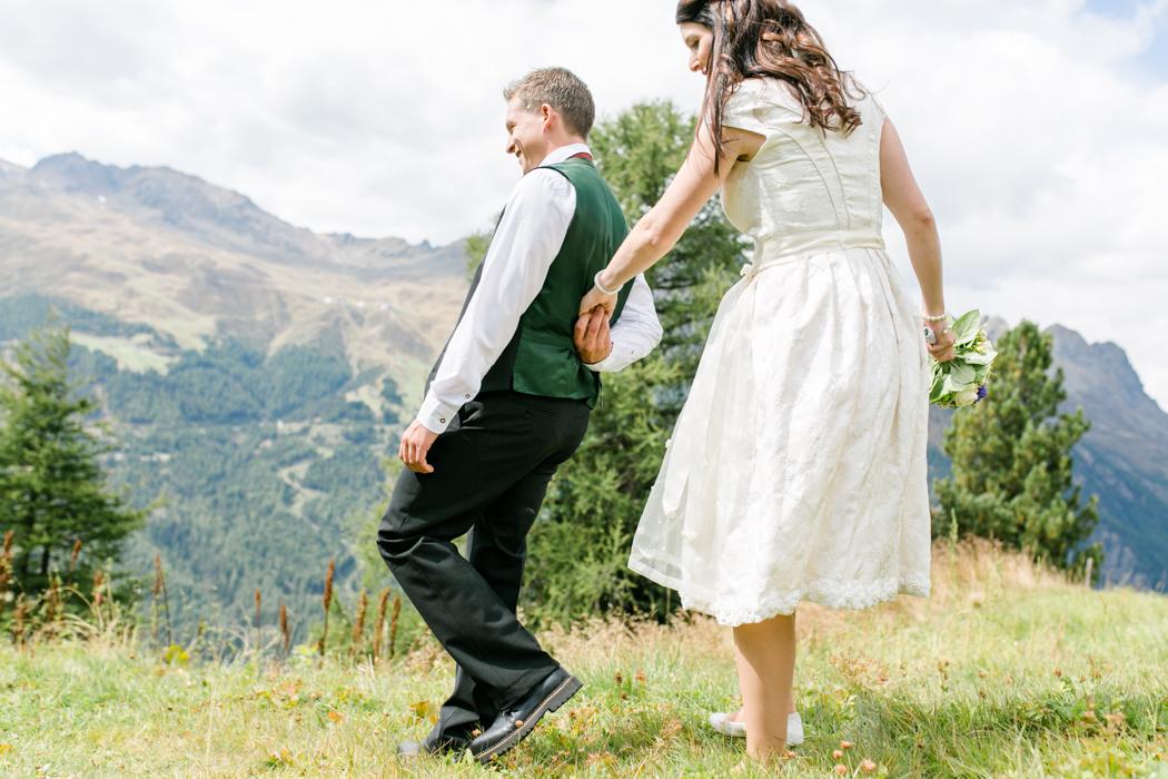 Brautpaar Hand in Hand auf der Alm